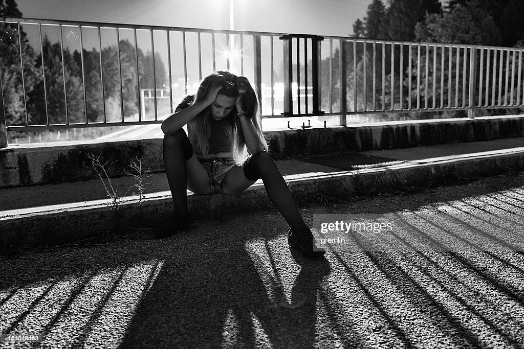 Young Depressed Woman Sitting On The Bridge Stock Photo