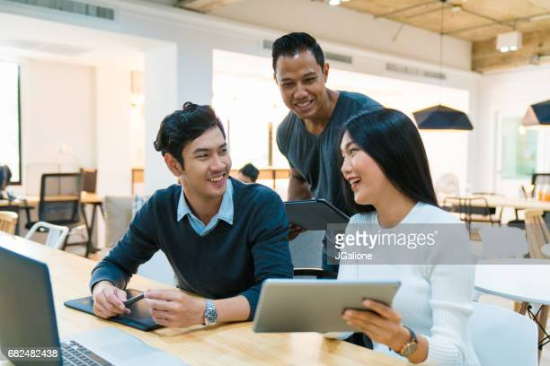 young design team in an informal meeting - asian and indian ethnicities stock pictures, royalty-free photos & images