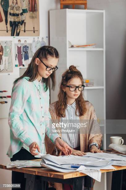 Young designer looking at sketches with female trainee in fashion studio