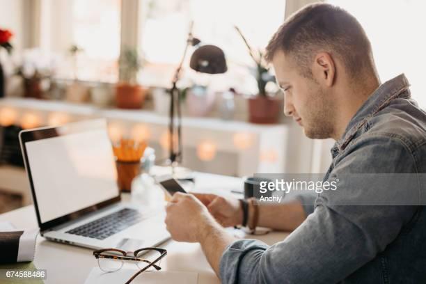 Young designer multitasking at home