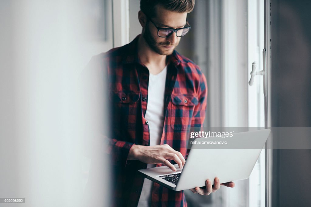 Young designer reading emails : Stock Photo