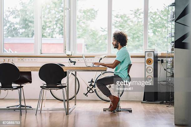 young designer sitting in office using laptop - funky stock pictures, royalty-free photos & images