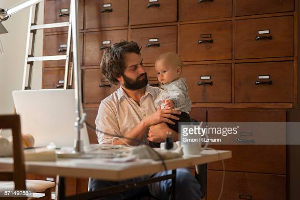 Young designer with baby son in home office