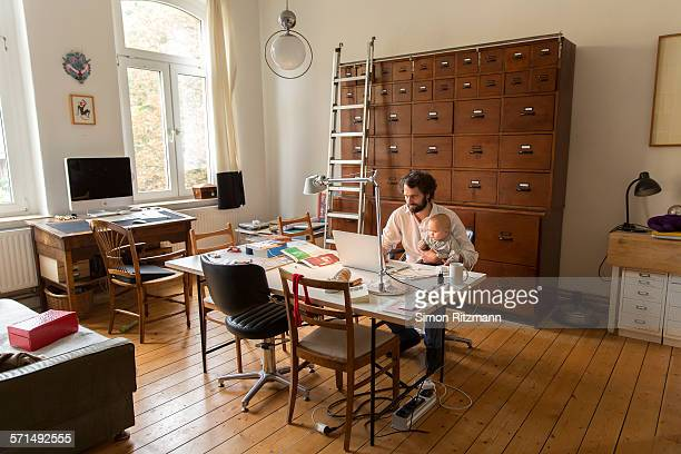 young designer working in home office with baby - innocence stock pictures, royalty-free photos & images