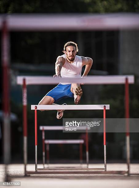 young determined athlete jumping hurdles on a race. - hurdling stock photos and pictures