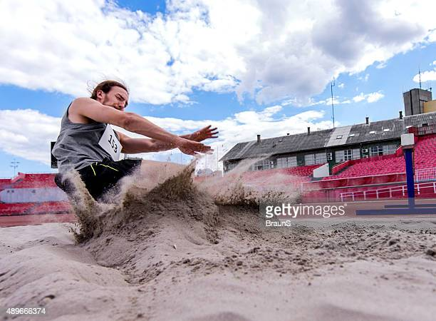 Young determined athlete landing in sand after a long jump.