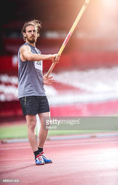 Young determined athlete preparing for a pole vault.