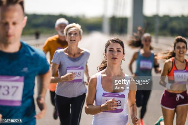 Young determined woman running a marathon race with other competitors on the road.