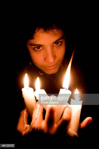 young devilish person holding candles in the dark - candle in the dark imagens e fotografias de stock