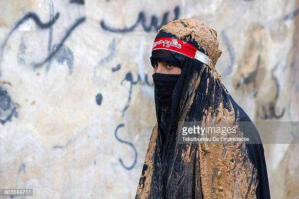 Young devote muslim woman, wearing a traditional black chador and a black veil, covered in mud, early in the morning, on the Day of Ashura, in the...