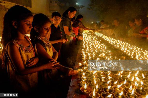 Young devotees perform a ritual by lighting diyas on the occasion of Karthika or Kartik month in Hyderabad on November 12 2019 Karthika or Kartik is...