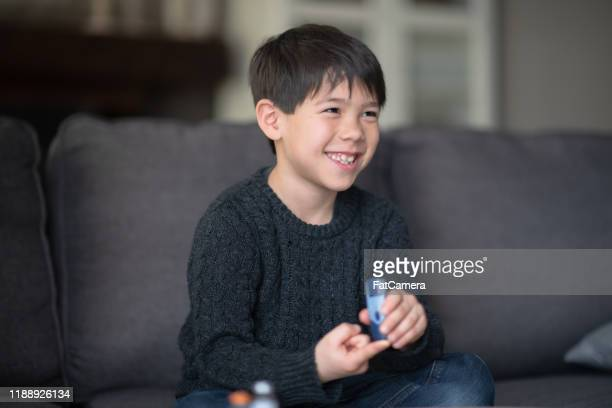 young diabetic asian boy testing his blood sugar stock photo - diabetes stock pictures, royalty-free photos & images