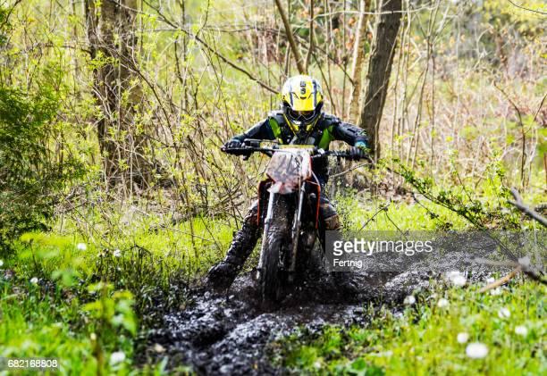 泥地を通り抜ける若いダートバイク
