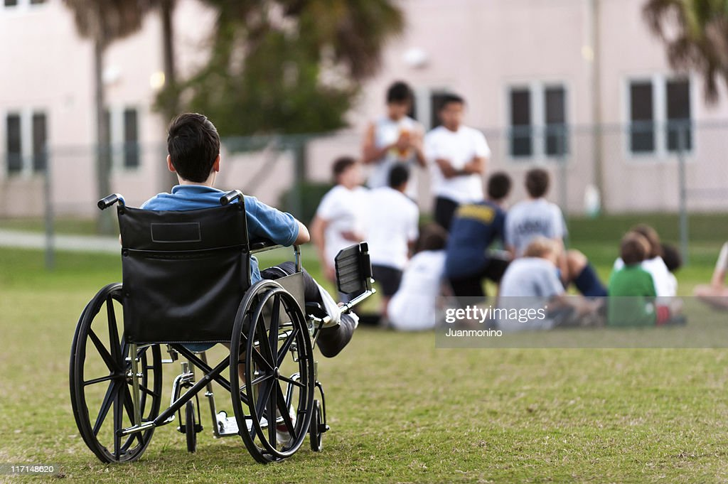 young disabled boy looking upon his peers leaving him out : Stock Photo