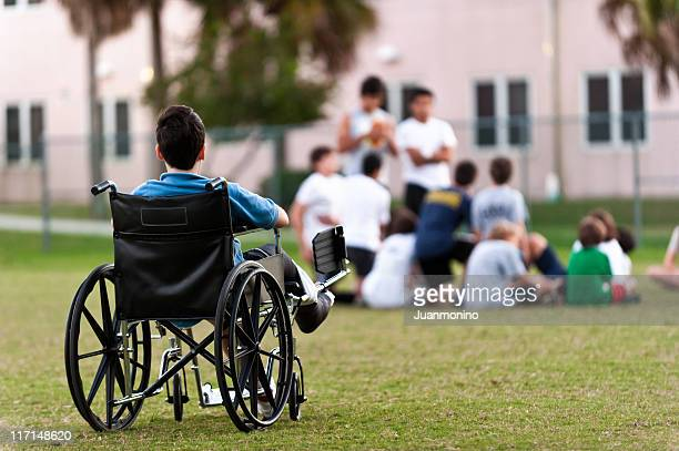 young disabled boy looking upon his peers leaving him out - prejudice stock photos and pictures