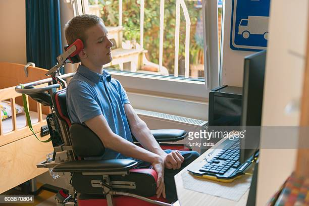 young disabled man playing computer game - paraplegic stock photos and pictures