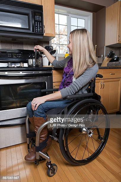 young disabled woman cooking in her kitchen - paraplegic stock photos and pictures