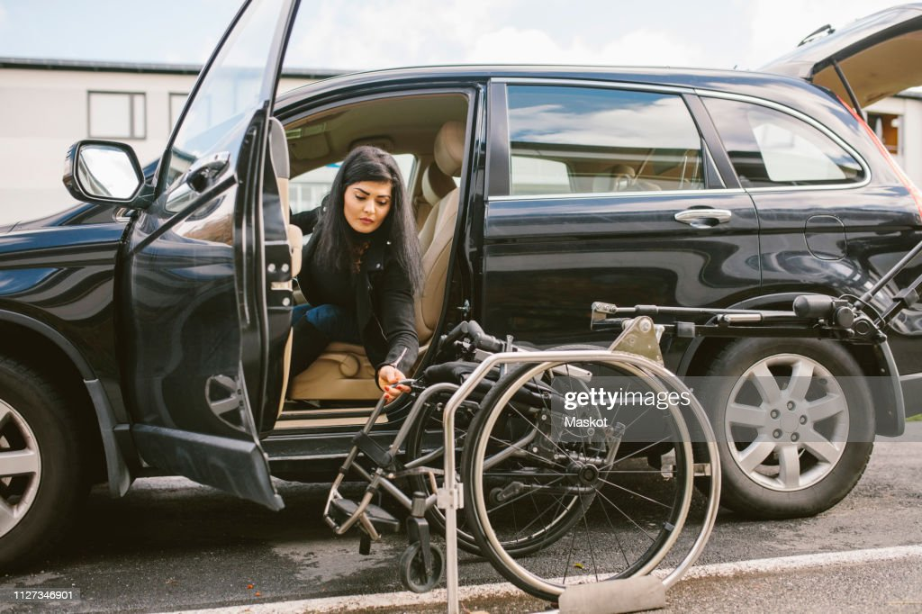 Young disabled woman holding wheelchair by car on roadside in city : Stock Photo