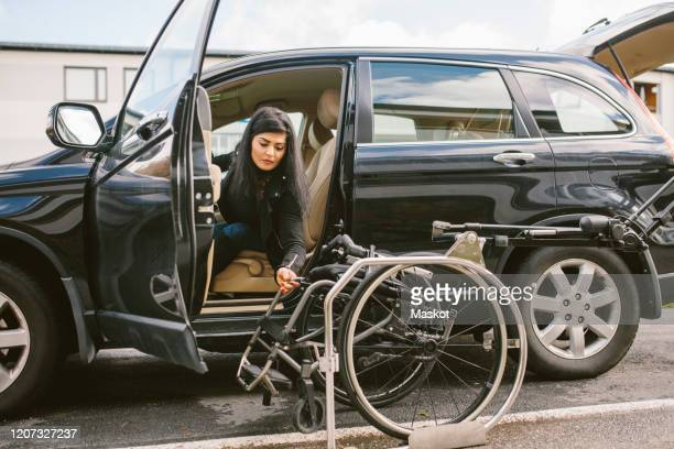 young disabled woman holding wheelchair by car on roadside in city - disability stock pictures, royalty-free photos & images