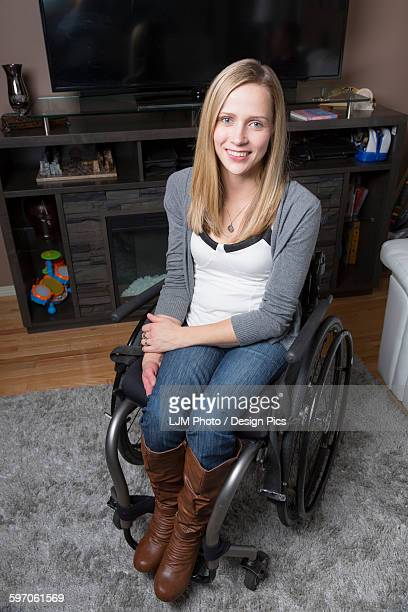 young disabled woman in a wheelchair in her living room - paraplegic stock photos and pictures
