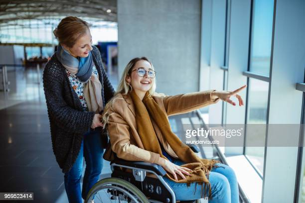 young disabled woman on wheelchair and mother waiting at airport - wheelchair stock pictures, royalty-free photos & images