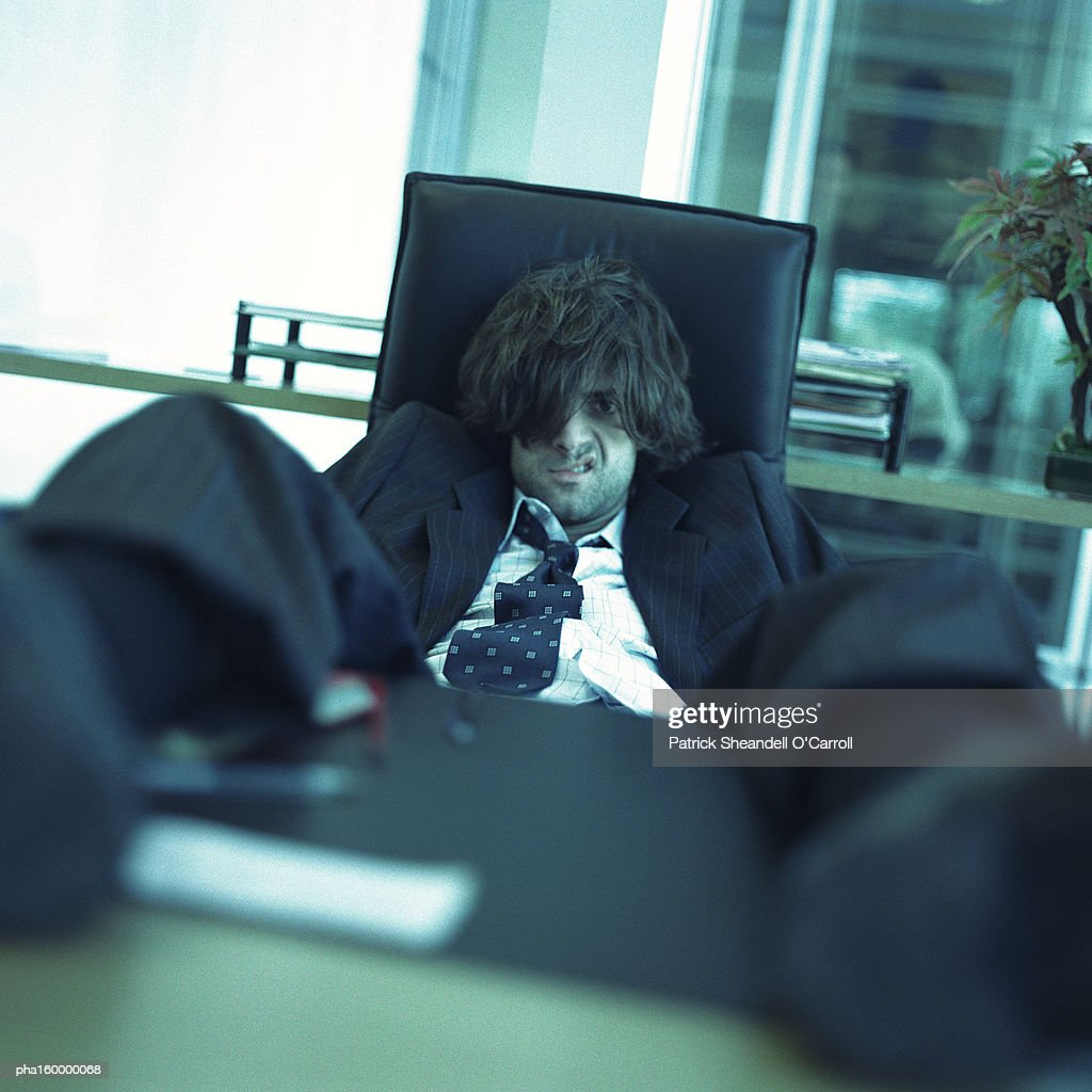 Young disheveled man sitting with feet on table. : Stockfoto