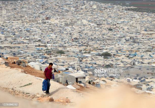 Young displaced Syrian returns from school to an overcrowded displacement camp near the village of Qah near the Turkish border in the northwestern...