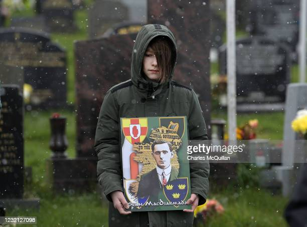 Young dissident republican supporter stands in Derry City cemetery during a 1916 wreath laying event as snow falls on April 5, 2021 in Londonderry,...