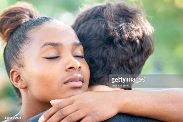 young diverse couple embracing - emotional support stock pictures, royalty-free photos & images