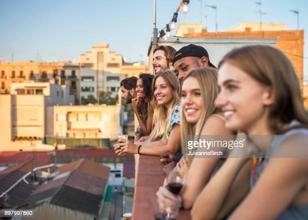 Joven grupo diverso de personas en la terraza viendo el atardecer