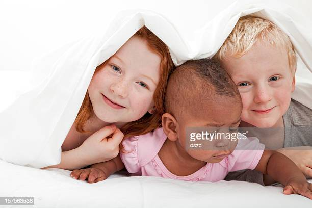 young diverse race children playing under the covers - black ginger baby stock photos and pictures