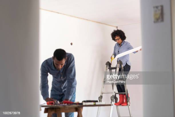 young diy couple renovating living room together - architectural cornice stock photos and pictures