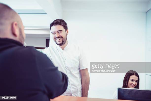 Joven Doctor y su asistente cita en recepción en clínica