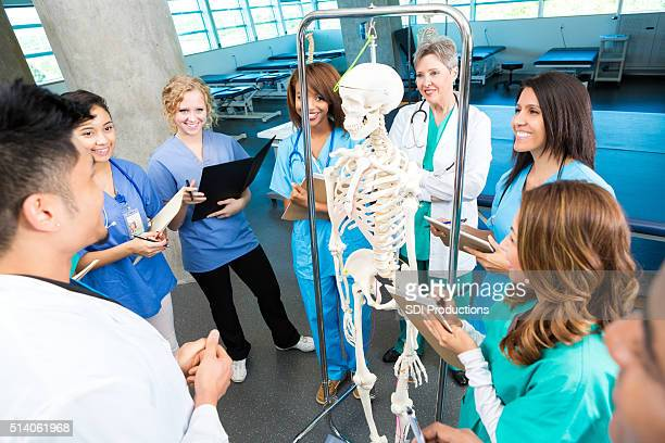 Young doctor discuses skeletal system to nursing students