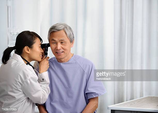 Young doctor examining a senior patient