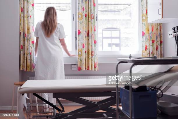 Young doctor in examination room looking through window