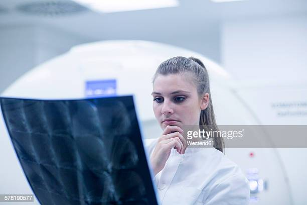 Young doctor in hospital looking at x-ray