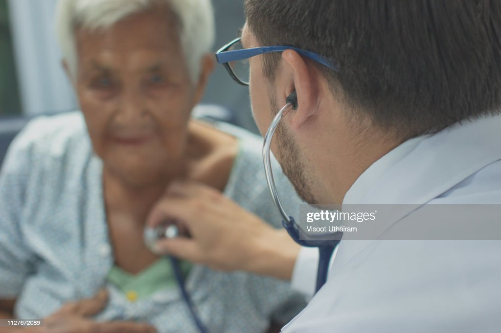 Young doctor listening heartbeat with stethoscope of old woman,Rural medicine concept. : Stock Photo