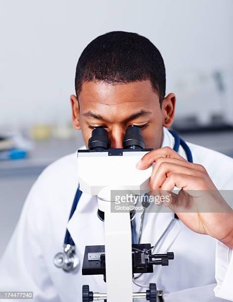 Junger Arzt auf der Suche durch Mikroskop