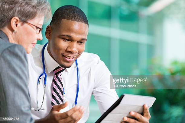 Young doctor meeting with senior adult patient in office