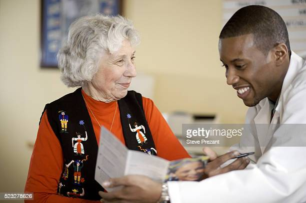 young doctor speaking with senior patient - gerontology stock pictures, royalty-free photos & images