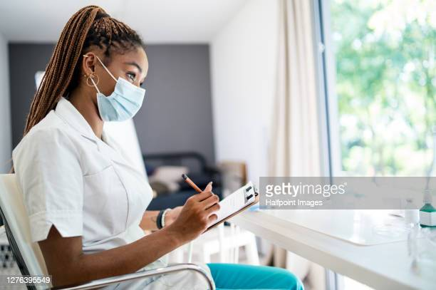 young doctor with clipboard writing, coronavirus vaccination concept. - form filling stock pictures, royalty-free photos & images