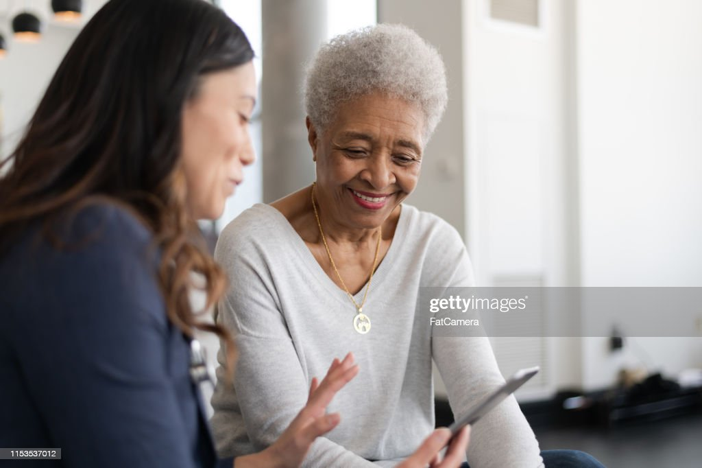 Young doctor with elderly patient : Stock Photo