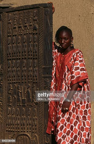 A young Dogon woman next to a carved door Sangha village Bandiagara Escarpment Mali