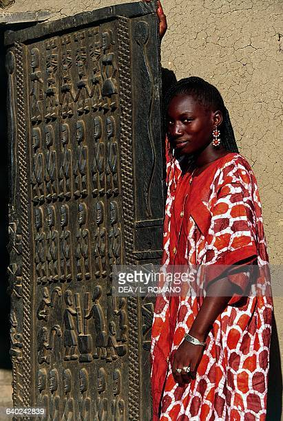 Young Dogon woman next to a carved door Sangha village Bandiagara Escarpment Mali
