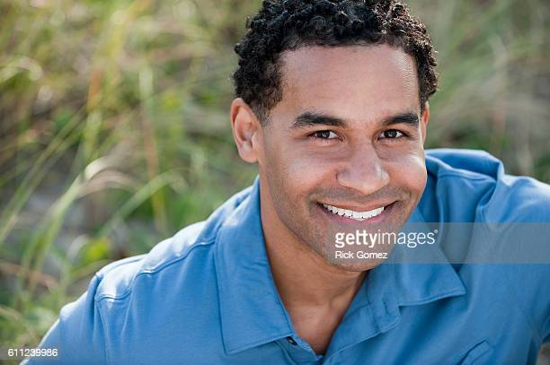 young dominican man smiling to camera in blue shirt. - dominican ethnicity stock photos and pictures