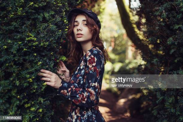 young dreamy woman walking in forest - robe à motif floral photos et images de collection