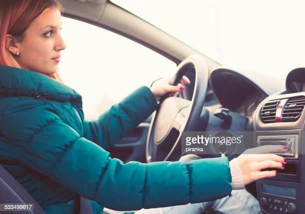 young driver changing radio stations - radio broadcasting stock pictures, royalty-free photos & images