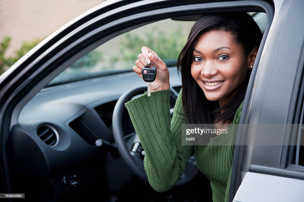 Young driver holding up car key : Stock Photo