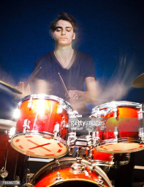 Young drummer in motion playing drums